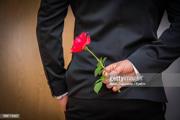 midsection of man holding red roses - ceremony stock pictures, royalty-free photos & images