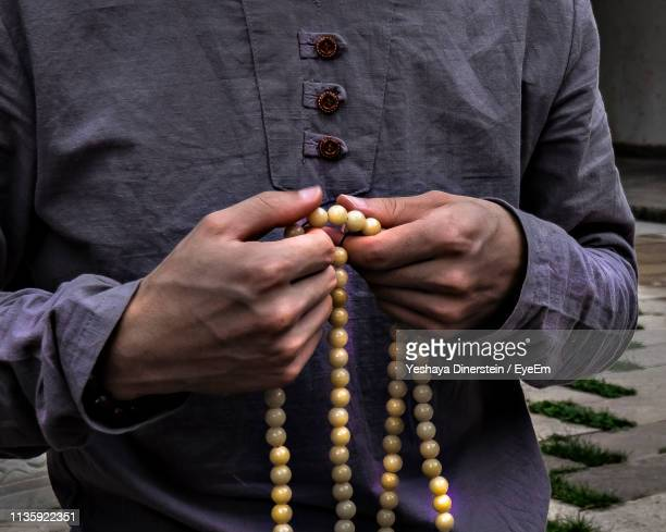 Midsection Of Man Holding Religious Beads While Standing Outdoors