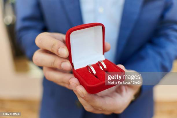 midsection of man holding rings in jewelry box - jewelry box stock pictures, royalty-free photos & images