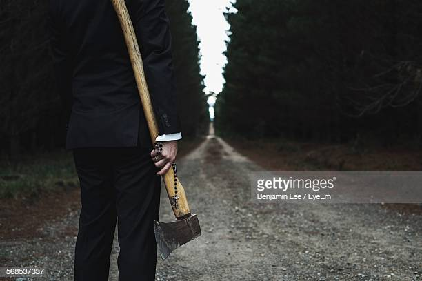 Midsection Of Man Holding Rosary Beads And Axe While Standing On Dirt Road