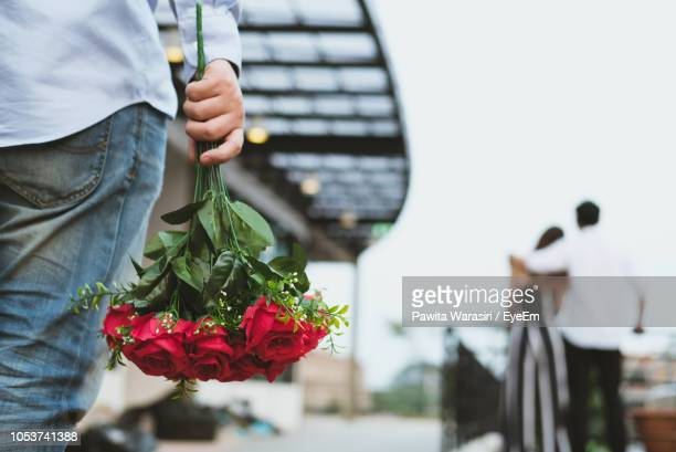midsection of man holding rose bouquet while couple standing against clear sky - bonding stock pictures, royalty-free photos & images