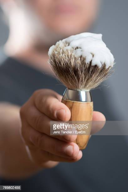 midsection of man holding shaving brush - shaving brush stock photos and pictures