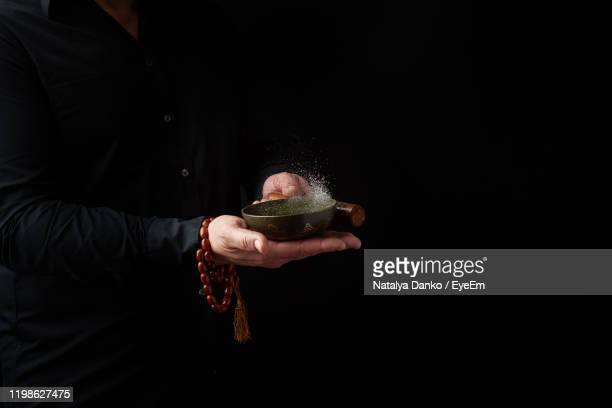 midsection of man holding singing bowl against black background - gong stock pictures, royalty-free photos & images