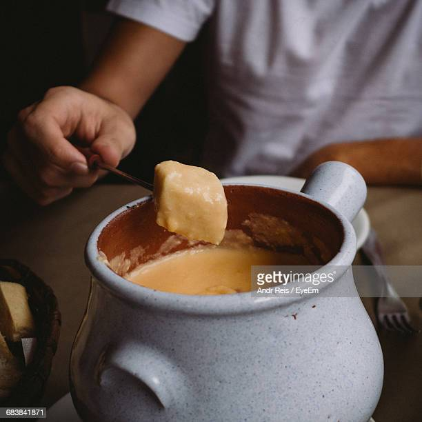 Midsection Of Man Holding Skewer On Cheese Fondue