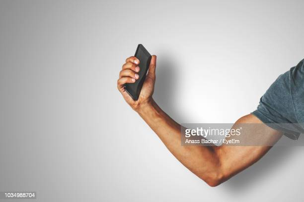 midsection of man holding smart phone against white background - arm stock pictures, royalty-free photos & images