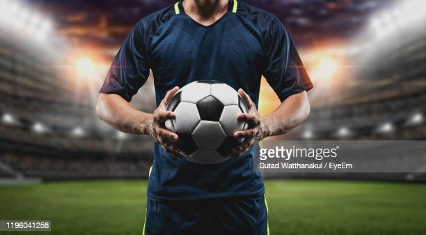 midsection of man holding soccer ball - midsection stock pictures, royalty-free photos & images