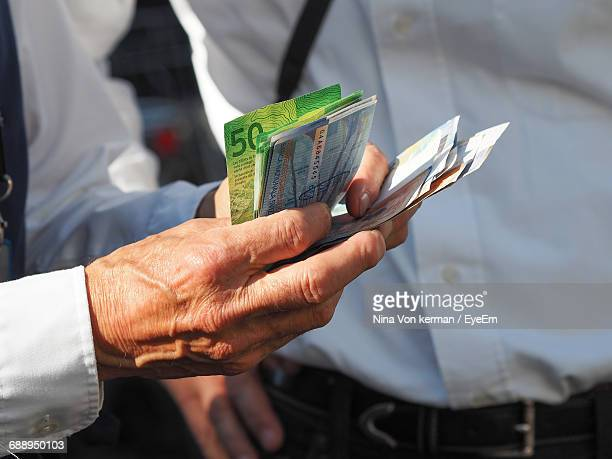 Midsection Of Man Holding Swiss Currencies