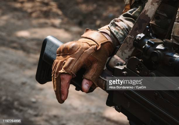 midsection of man holding weapon outdoors - leather glove stock pictures, royalty-free photos & images