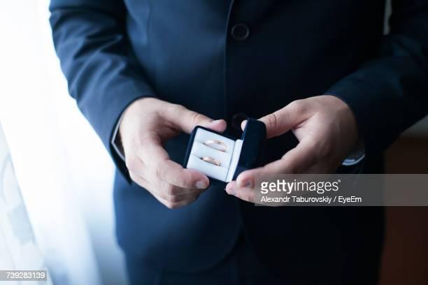 Midsection Of Man Holding Wedding Rings In Box By Curtain
