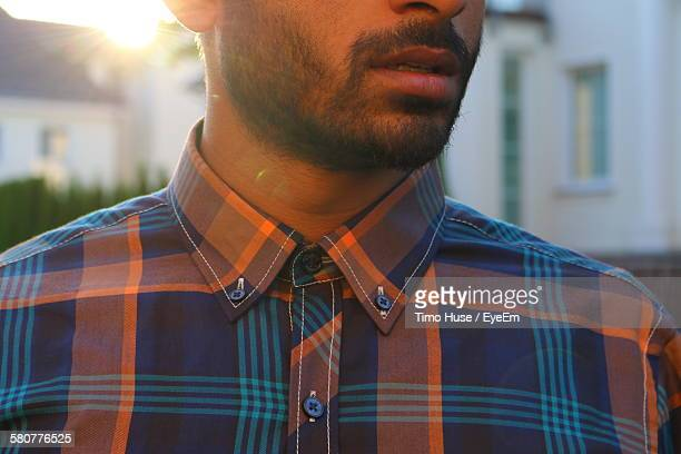 Midsection Of Man In Button Down Shirt Standing Against Building