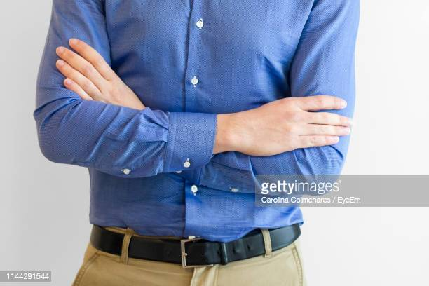 midsection of man in formal standing against white background - blauwe riem stockfoto's en -beelden