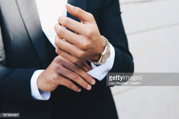 midsection of man in suit adjusting sleeves - adjusting stock pictures, royalty-free photos & images