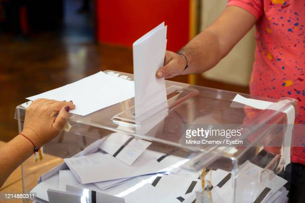 midsection of man inserting papers in ballot box - ballot box stock pictures, royalty-free photos & images