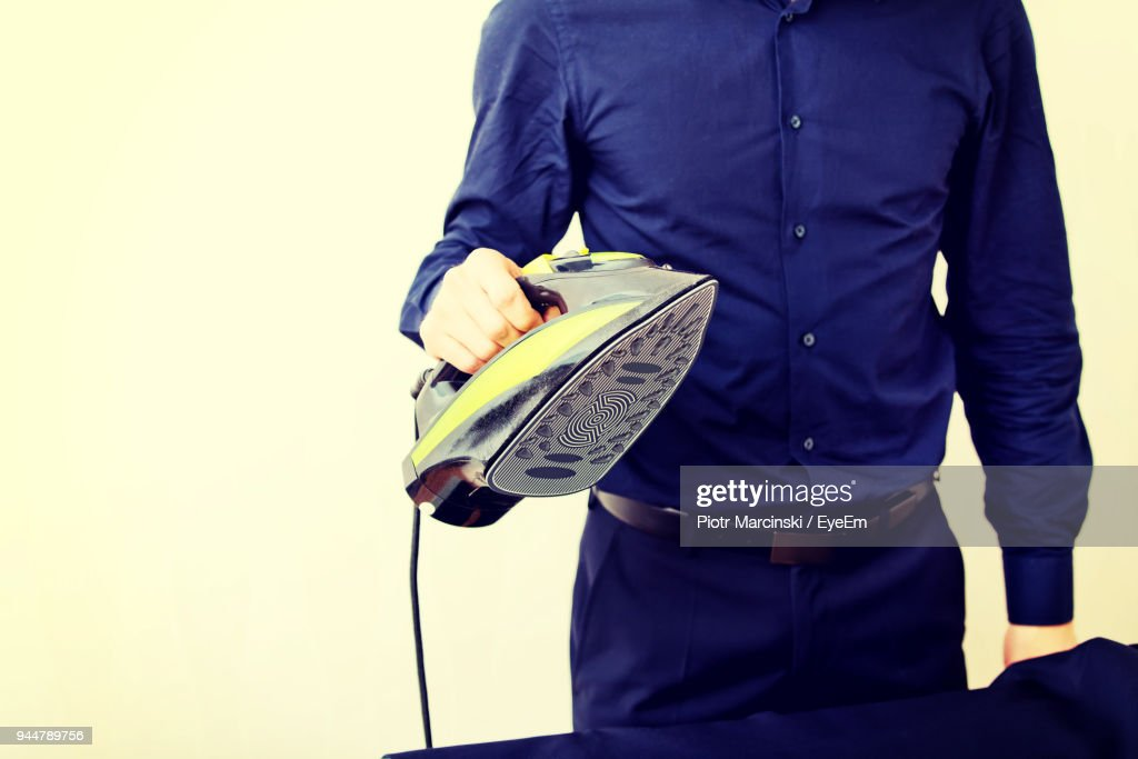 Midsection Of Man Ironing Clothes : Stock Photo