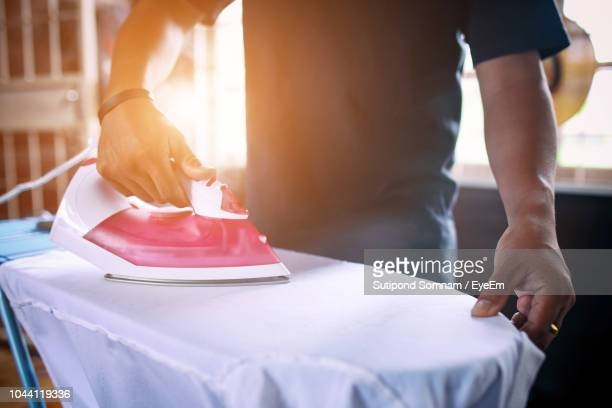 Midsection Of Man Ironing Shirt At Home