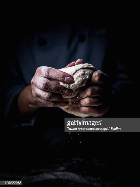 midsection of man kneading dough in darkroom - dough stock pictures, royalty-free photos & images