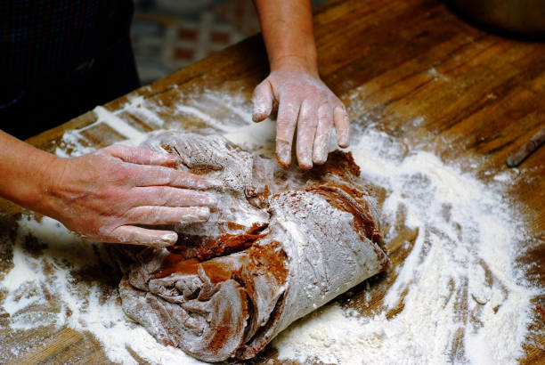 Midsection Of Man Kneading Dough On Table