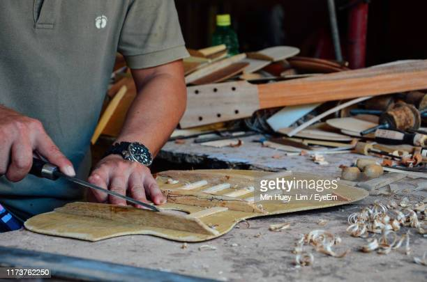 midsection of man making guitar on table - cebu province stock pictures, royalty-free photos & images