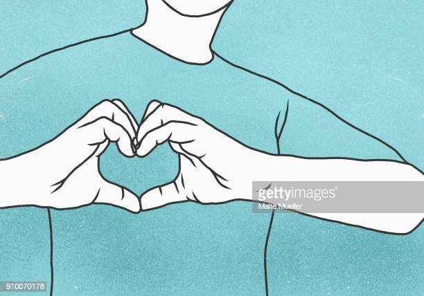 Midsection of man making heart shape against blue background