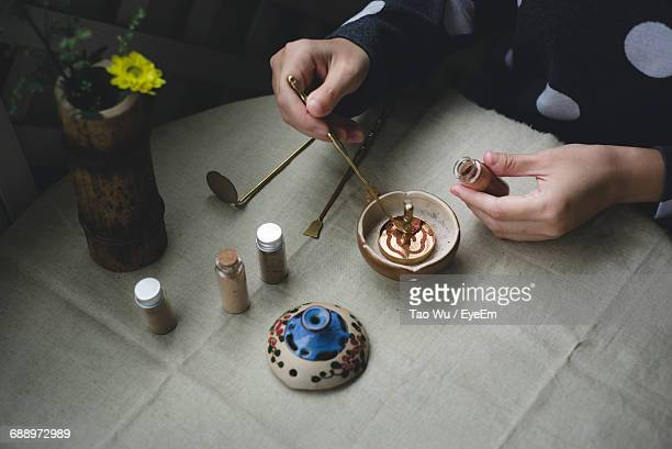 midsection of man making incense on table - incense stock photos and pictures