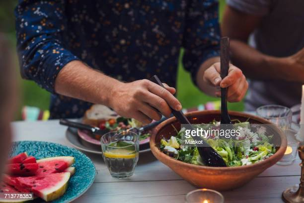midsection of man mixing salad at table during garden party - porzione di cibo foto e immagini stock