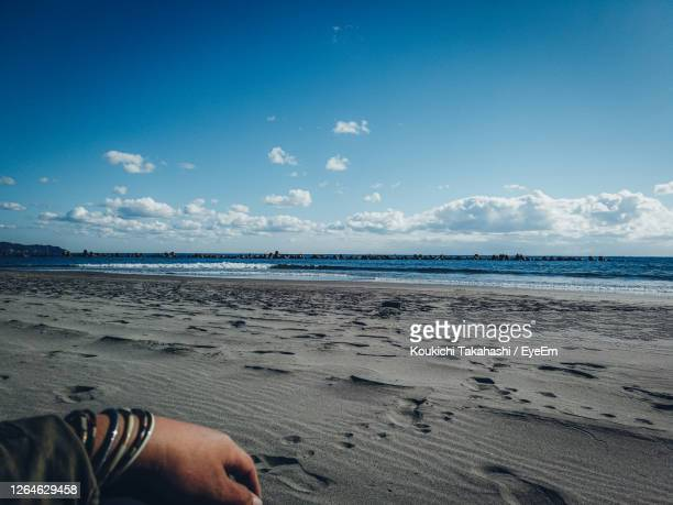 midsection of man on beach against sky - koukichi stock pictures, royalty-free photos & images