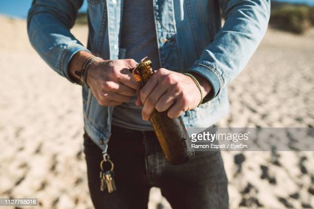 midsection of man opening bottle on beach - ventenne foto e immagini stock