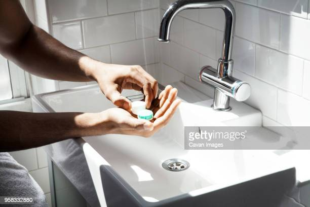 midsection of man opening contact lens case in bathroom - contact lens stock pictures, royalty-free photos & images
