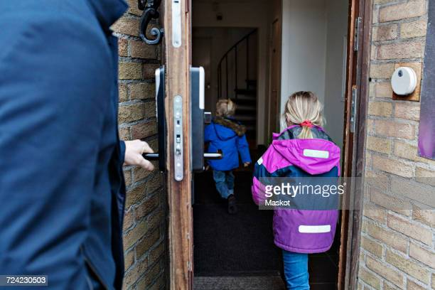 Midsection of man opening house door for children