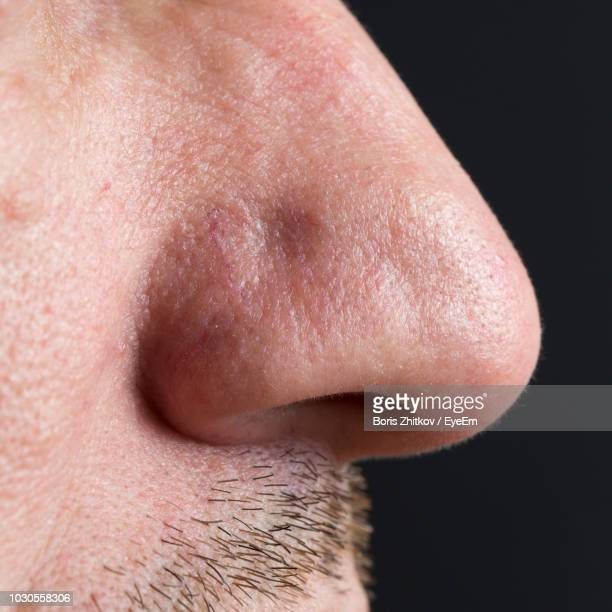 midsection of man over black background - nose stock pictures, royalty-free photos & images