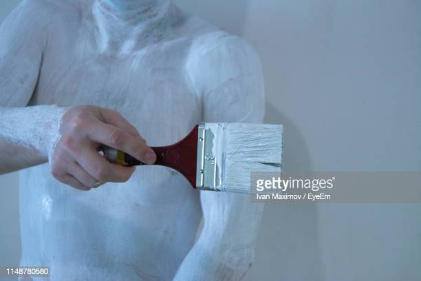midsection of man painting body - body paint stock pictures, royalty-free photos & images