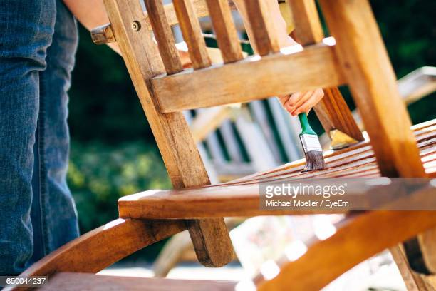 Midsection Of Man Painting Chair During Sunny Day