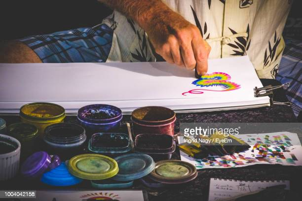 Midsection Of Man Painting On Paper At Table