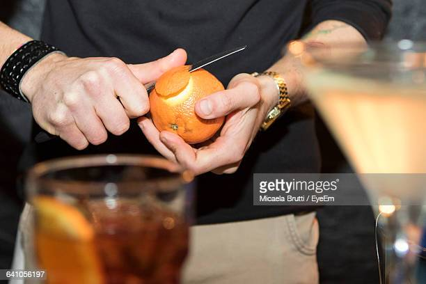 Midsection Of Man Peeling Orange In Front Of Cocktails