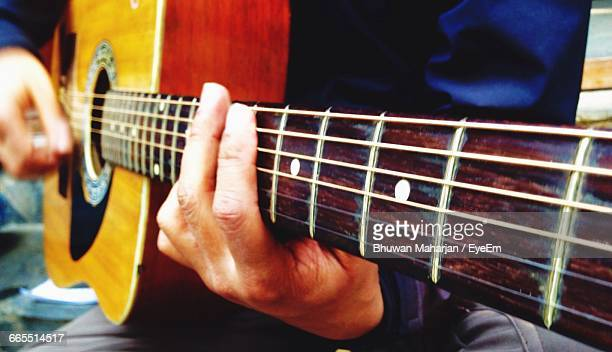 Midsection Of Man Playing Acoustic Guitar