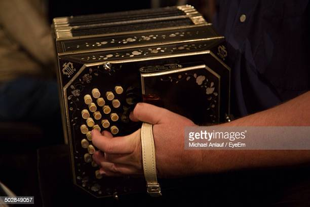 Midsection of man playing bandoneon