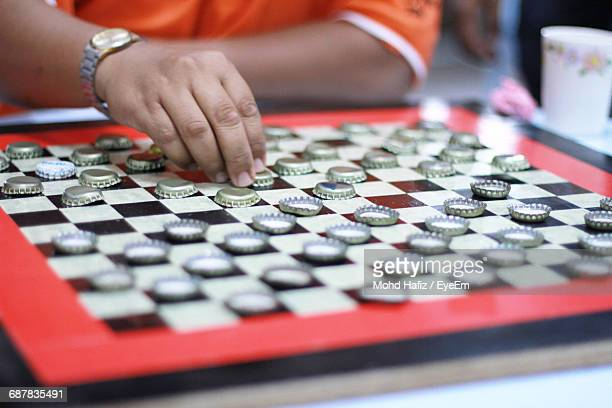 Midsection Of Man Playing Bottle Cap Checkers