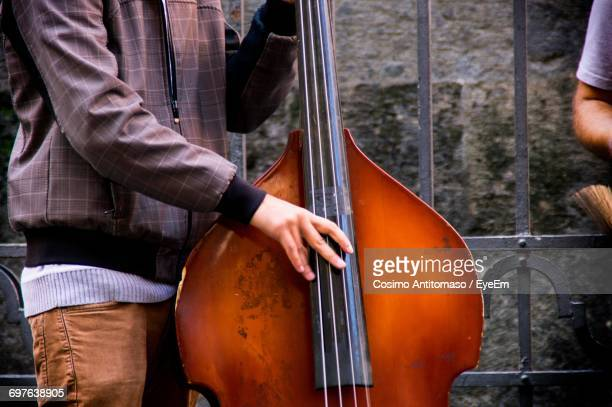Midsection Of Man Playing Double Bass