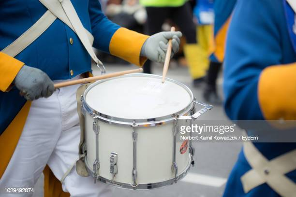 midsection of man playing drum on street during carnival - marching band stock pictures, royalty-free photos & images