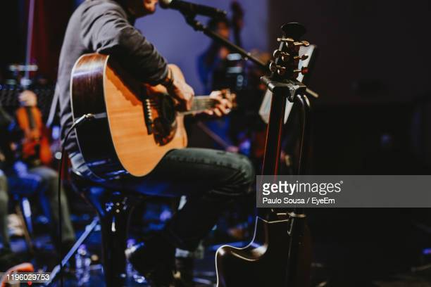 midsection of man playing guitar at music concert - acoustic guitar stock pictures, royalty-free photos & images