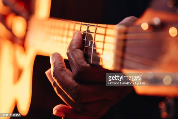 midsection of man playing guitar at music concert - hamiltonmusical stockfoto's en -beelden