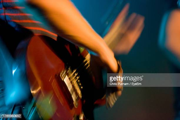 midsection of man playing guitar at music concert - chris putnam stock pictures, royalty-free photos & images