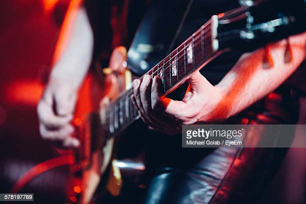 Midsection Of Man Playing Guitar At Nightclub