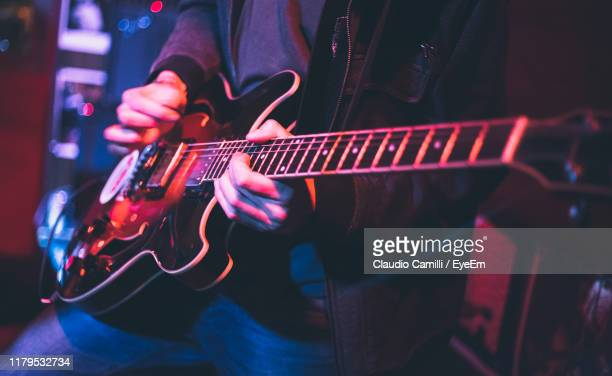midsection of man playing guitar during concert - ポップコンサート ストックフォトと画像
