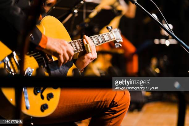 midsection of man playing guitar on stage - ギタリスト ストックフォトと画像