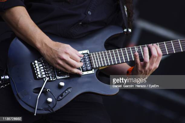 midsection of man playing guitar - guitar stock pictures, royalty-free photos & images