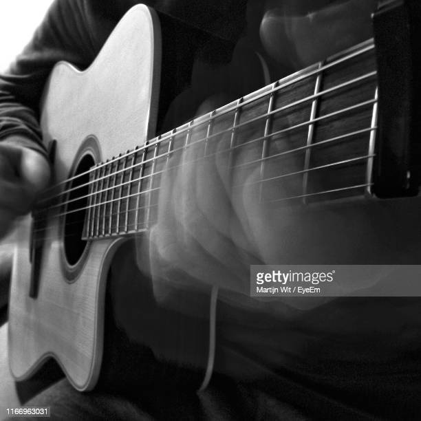 midsection of man playing guitar - plucking an instrument stock pictures, royalty-free photos & images