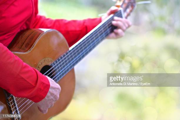 midsection of man playing guitar - antonella di martino foto e immagini stock