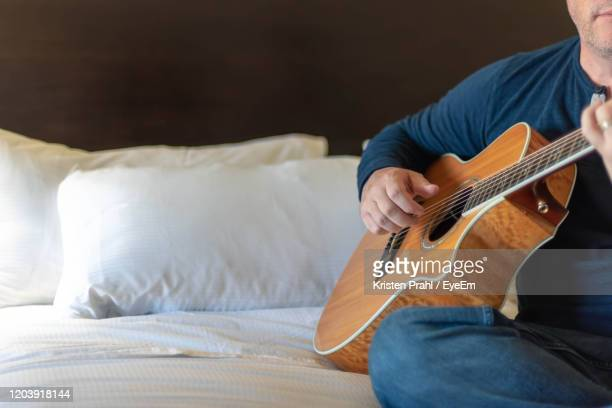midsection of man playing guitar - ポートヒューロン ストックフォトと画像
