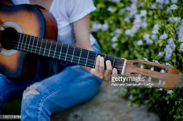 midsection of man playing guitar - musical instrument string stock pictures, royalty-free photos & images
